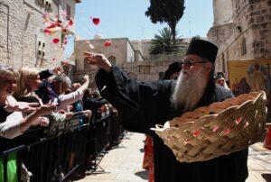 Greek Orthodox priest scatters rose petals.  Source